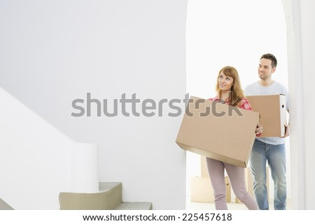Couple carrying moving boxes - stock photo