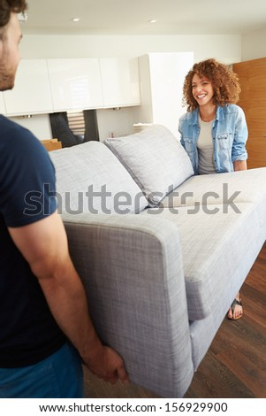 Couple Carrying Sofa As They Move Into New Home - stock photo