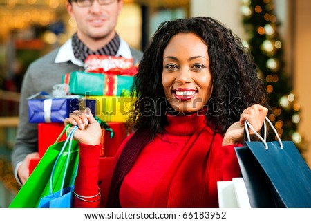 Couple - Caucasian man and black woman - with Christmas presents, gifts and shopping bags - in a mall in front of a Christmas tree - stock photo