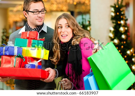 Couple - Caucasian man and woman - with Christmas presents, gifts and shopping bags - in a mall in front of a Christmas tree - stock photo