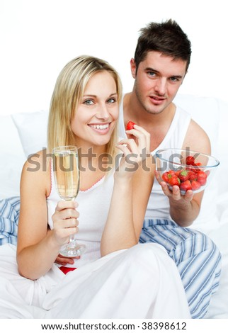 Couple celebrating an engagement with strawberries and champagne in bed