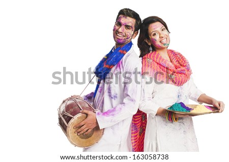 Couple celebrating Holi with colors and a drum - stock photo