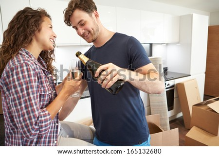 Couple Celebrating Moving Into New Home With Champagne - stock photo