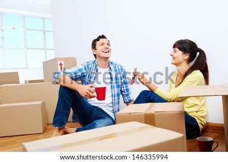 couple celebrating new home handing keys and moving boxes - stock photo