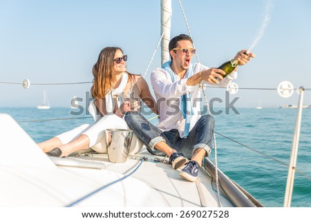 Couple celebrating with champagne on a boat .Attractive man uncorking champagne and having party with girlfriend on vacation.Two young tourists having fun on boat tour in the summertime - stock photo