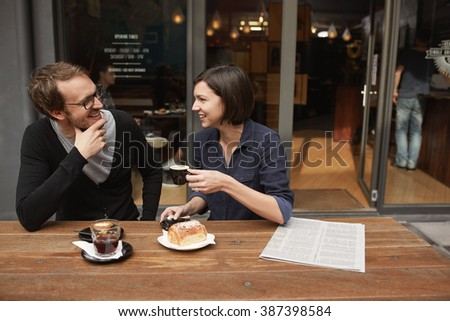 Couple chatting over coffee at outdoor modern cafe