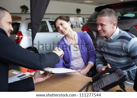 Couple chatting with a car salesman in a car shop - stock photo