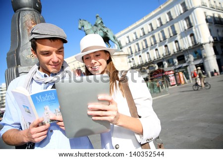 Couple checking on tourist information in Madrid - stock photo