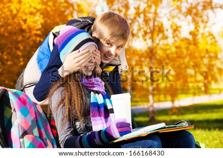Couple children, boy covers girls face with palms and laughing making a surprise, gal sitting on the bench in autumn park - stock photo