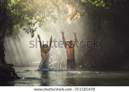 Couple children playing catch duck in river