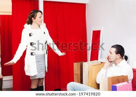 Couple choosing coat in fitting-room at boutique - stock photo