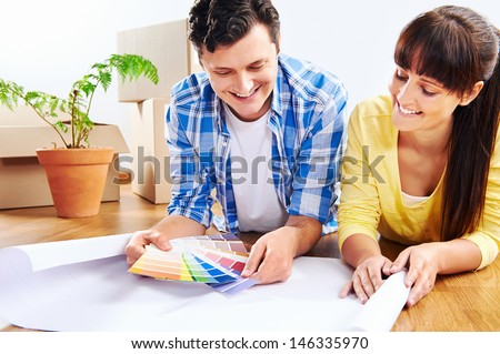 couple choosing paint colour from swatch in new home apartment together - stock photo