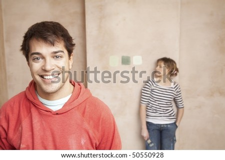 Couple choosing paint colours in unrenovated room - stock photo