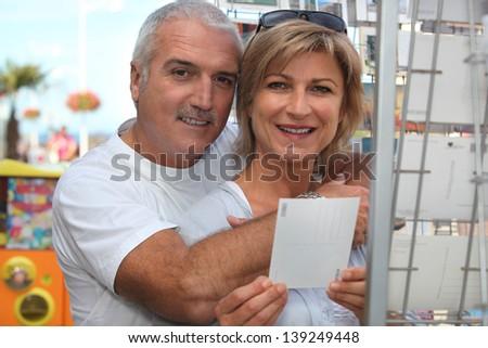 Couple choosing postcard - stock photo