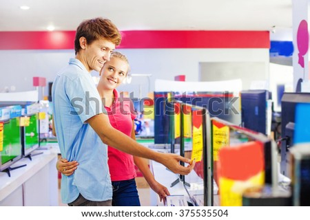 couple choosing tv in a shop - stock photo