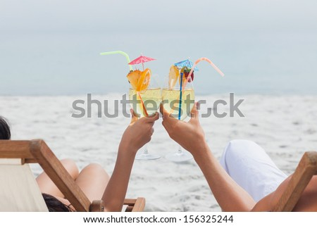 Couple clinking glasses of cocktail on beach in front of ocean - stock photo