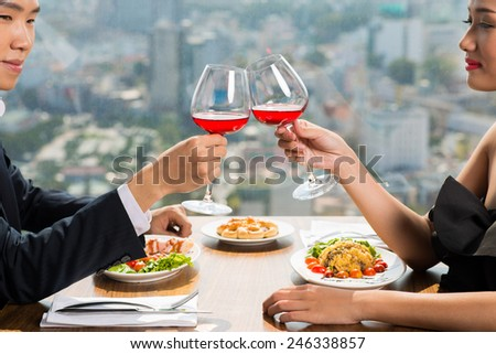 Couple clinking glasses with red wine