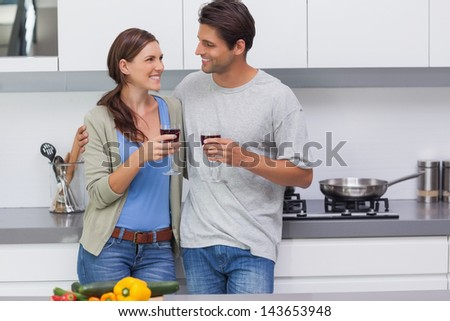 Couple clinking their glasses of red wine in the kitchen - stock photo