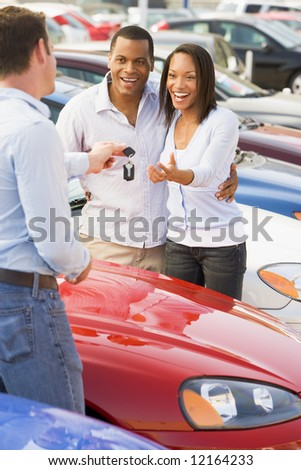 Couple collecting new car keys from salesman on lot
