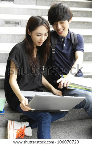 Couple college friends sitting holding laptop with books on campus - stock photo