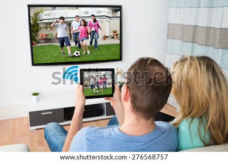 Couple Connecting Television And Digital Table Through Wifi Signal At Home