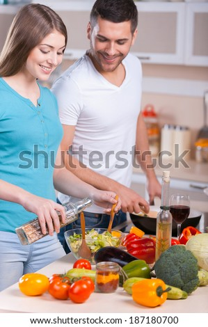 Couple cooking dinner. Happy young couple cooking dinner in the kitchen - stock photo