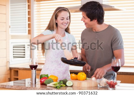 Couple cooking dinner in their kitchen - stock photo