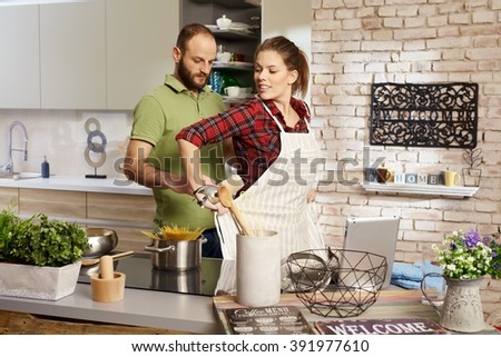Couple cooking in kitchen, woman putting on apron, man tieing it. - stock photo