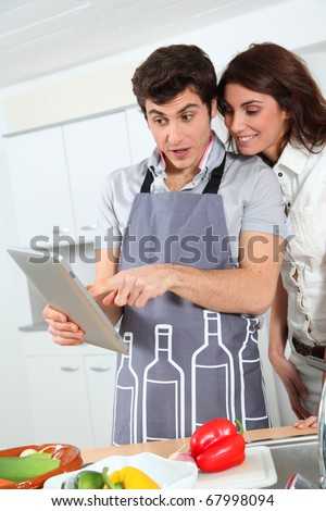 Couple cooking with electronic tab