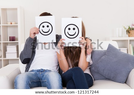 Couple covered faces with smiley white paper. - stock photo