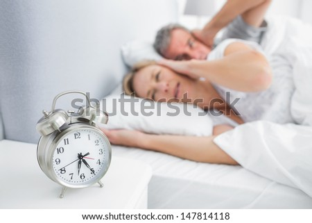 Couple covering their ears from alarm clock noise in bedroom at home - stock photo