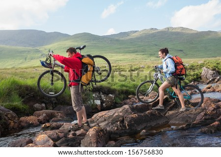 Couple crossing a stream holding their bikes in the mountains - stock photo