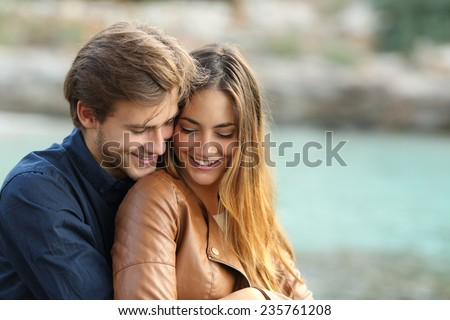 Couple cuddling affectionate on the beach in winter with the sea in the background - stock photo
