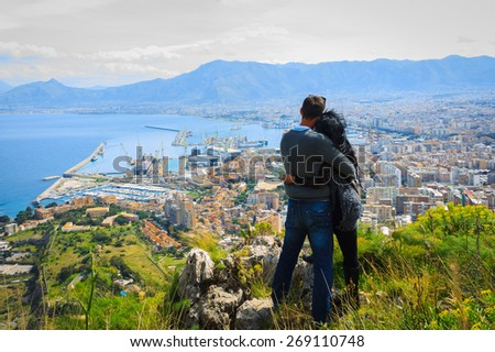 Couple cuddling and enjoying view above city on top of hill. - stock photo