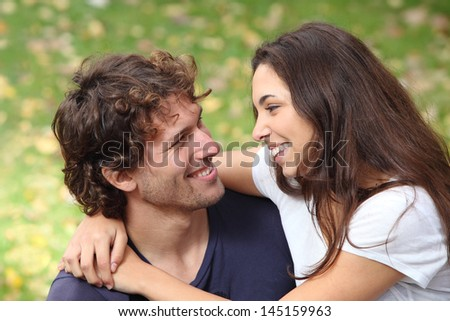 Couple cuddling and flirting in a park with a green unfocused background