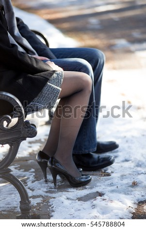 Couple cuddling on park bench together in the winter.