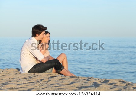 Couple cuddling sitting on the sand of the beach watching the sea - stock photo