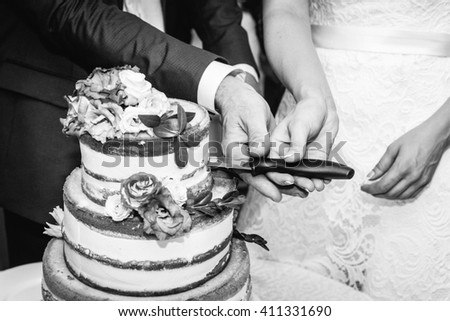 Couple cut the wedding cake, black and white photography. Naked cake, decorated with flowers. End of the wedding banquet. - stock photo