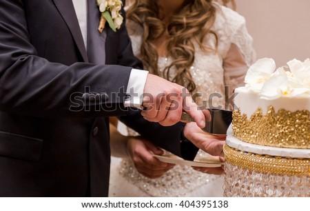 Couple cutting their wedding cake. - stock photo