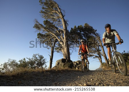 Couple cycling along mountain path, front view, surface level - stock photo