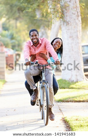 Couple Cycling Along Suburban Street Together