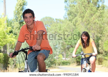Couple cycling in the countryside - stock photo