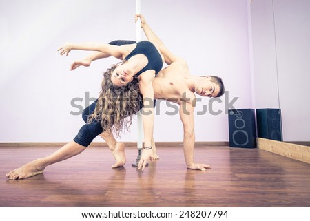 Couple dancing at pole in a fitness studio - Ballet dancers working out - stock photo