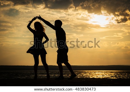 Couple dancing at sunset salsa / brazilian zouk. Lovers, dance partners spinning, latin festival dance concept.