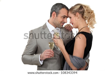 Couple dancing with glasses of champagne - stock photo