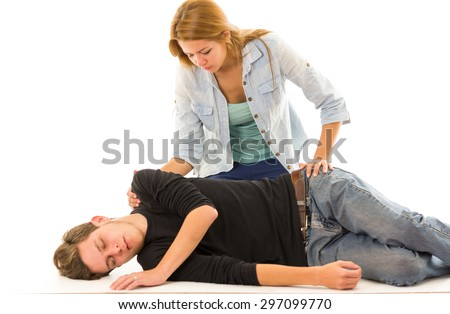 Couple demonstrating first aid techniques with male patient lying in recovery position and female sitting above him. - stock photo