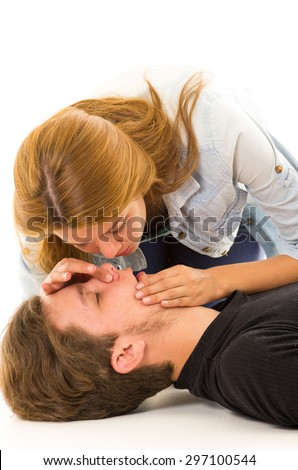 Couple demonstrating first aid techniques with woman about to perform mouth resuscitation. - stock photo