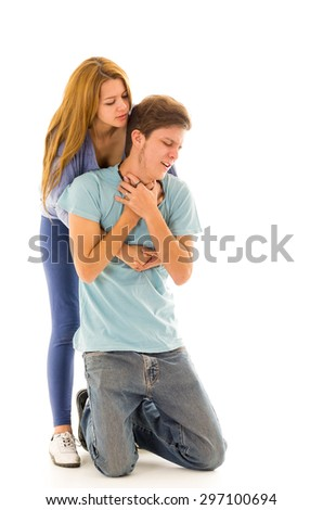 Couple demonstrating first aid techniques with woman performing heimlich on choking male. - stock photo