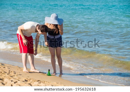 Couple discovering a bottle washed ashore, will it contain a message? - stock photo