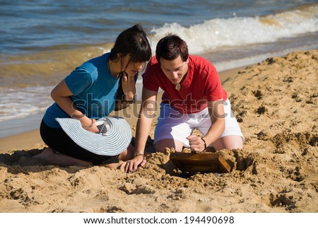 Couple discovering a treasure on the beach, a concept - stock photo